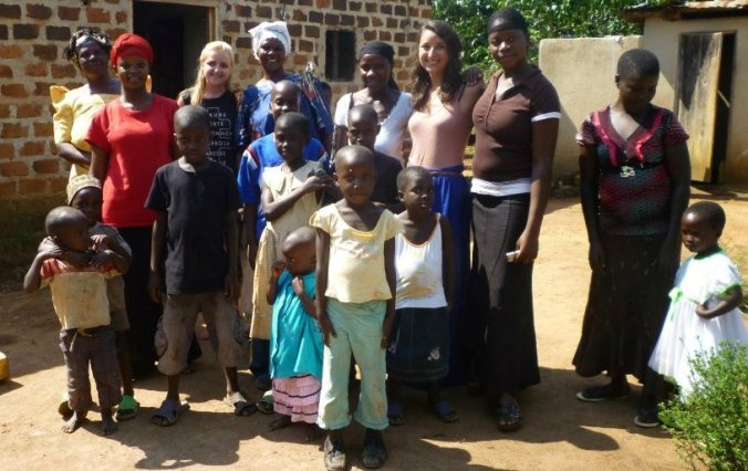 Phoebe Tansley and friend Emily Fulda with local residents in Kampala, Uganda